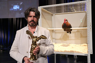 Koen Vanmechelen met de Prix Ars Electronical 2013. The Cosmopolitan Chicken Project