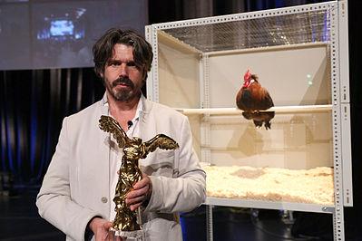Koen Vanmechelen met de Prix Ars Electronical 2013. The Cosmopolitan Chicken Project